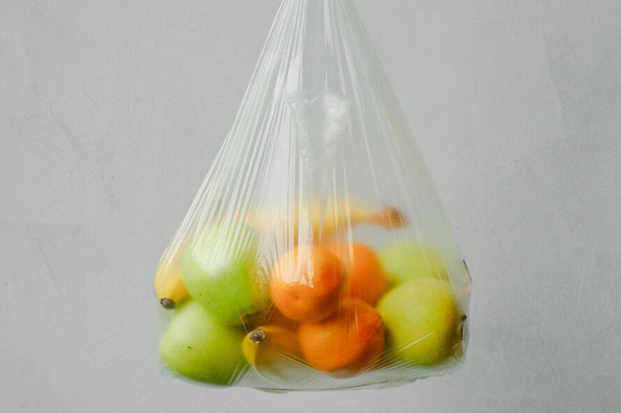 a plastic bag full of green apples, oranges and bananas