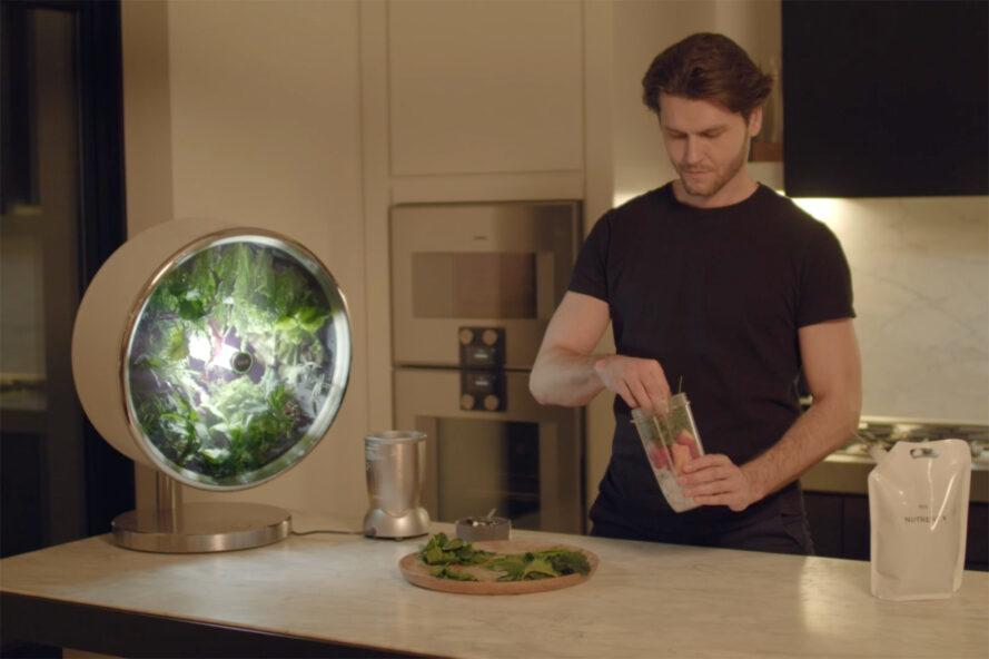 person grabbing fresh greens from a round indoor garden to add to a smoothie