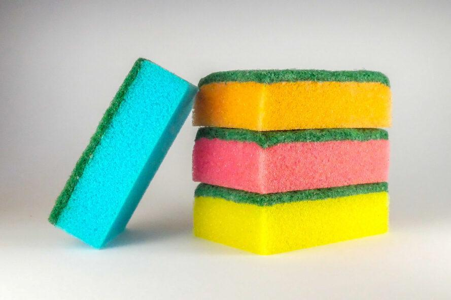 three sponges in the colors orange, pink and yellow with a blue sponge leaning against the stack