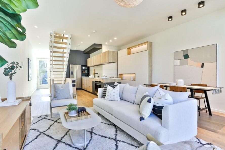 main living space with white sofa and printed rug
