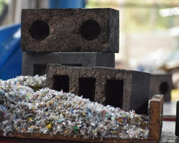 silica plastic blocks stacked next to a pile of shredded plastic waste