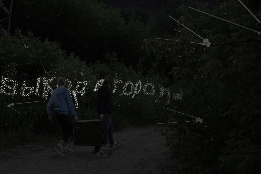 a night-time shot of two people carrying something on a dirt path, surrounded by trees set up with oscillation tracking devices. white lights spell out words in what appears to be Russian