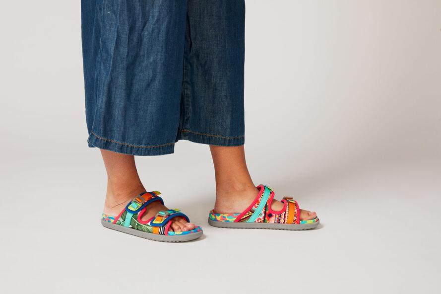 a person in loose blue jeans wearing a pair of multi-colored sandals, with both feet on the ground