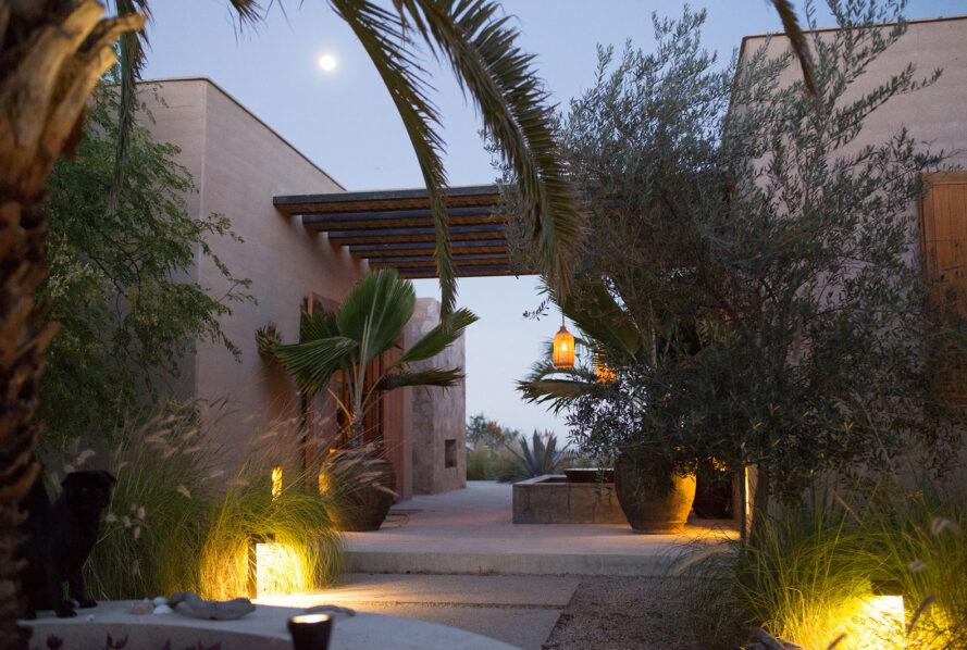 a stone and rammed earth home surrounded by foliage and lights