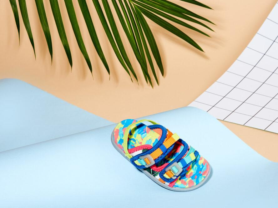 a multi-colored sandal propped up against a wavy, blue paper background, with a green leaf behind it