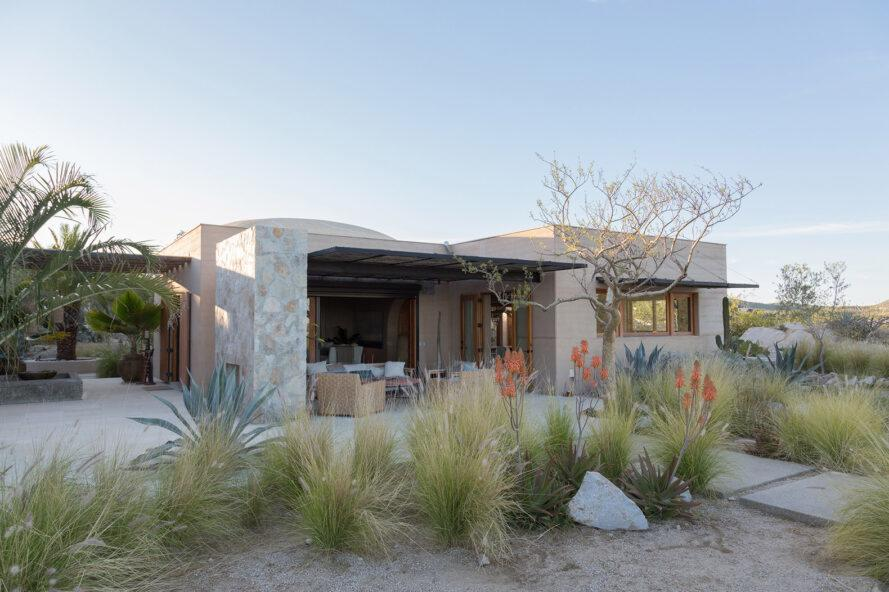a stone and rammed earth home surrounded by desert landscape