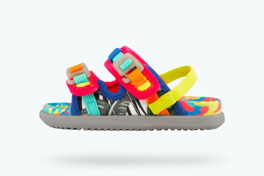 a kids-size multi-colored sandal with pink, orange and blue accents with a yellow heel strap against a white background
