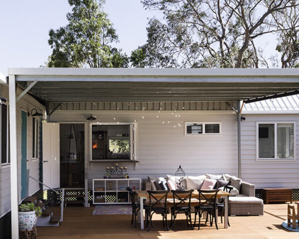 a one-level tiny home with a porch and overhanging shade. the porch is decorated with furniture, including a table and chairs. a mother and her two daughters sit on the porch, smiling for the camera.