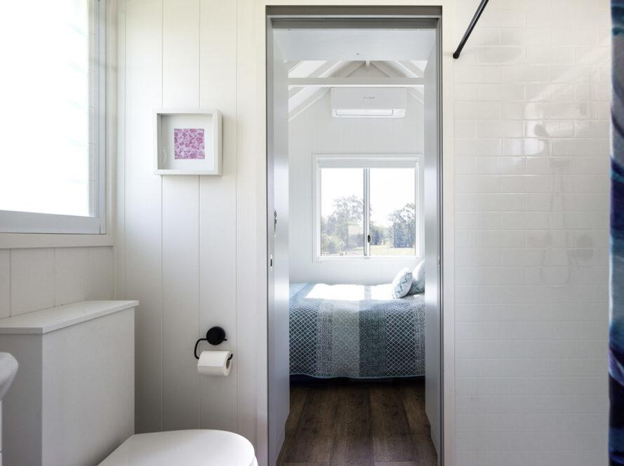 a bathroom with a white toilet visible to the left. the bathroom door is open and looking into a bedroom with a blue patterned comforter and windows.