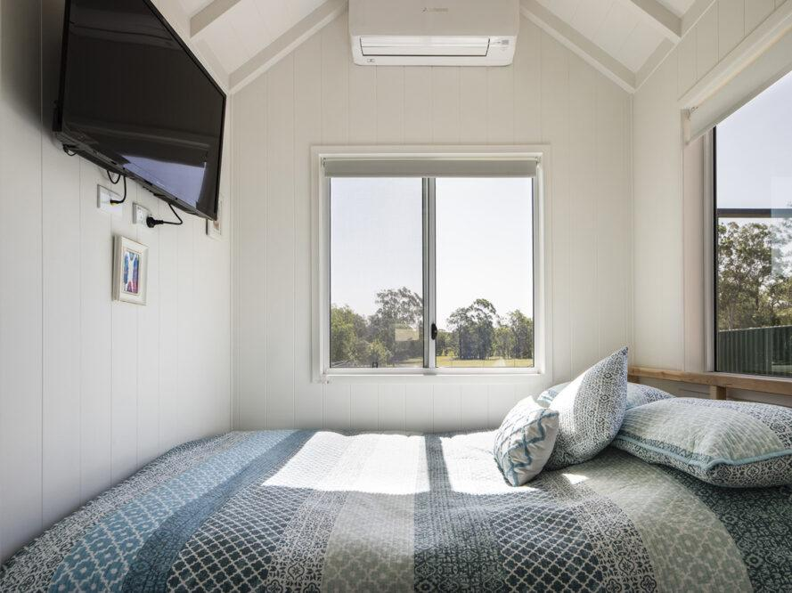 a bedroom with a blue patterned comforter and windows that look out onto greenery. to the left, a TV is mounted on the wall.