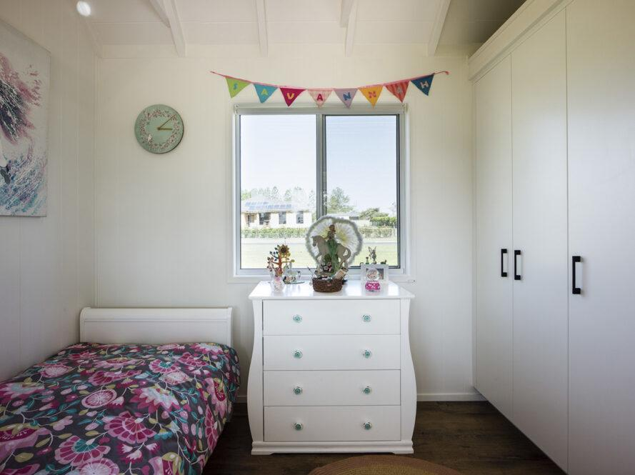 "a child's bedroom. to the left, a pink flower patterned bed spread covers a bed. above the bed is a blue-green clock, and to the left of the bed is a piece of abstract art. in the middle of the wall is a white dresser with decorations on top, and windows above the dresser. to the left are tall, white storage cabinets. a banner above the windows reads ""Savannah."""