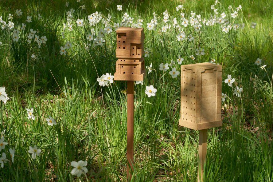 two wood beehives on stakes in a garden