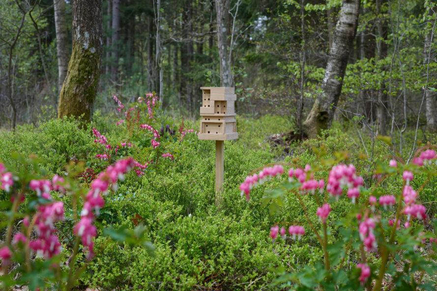 wood beehive on a stake in a meadow