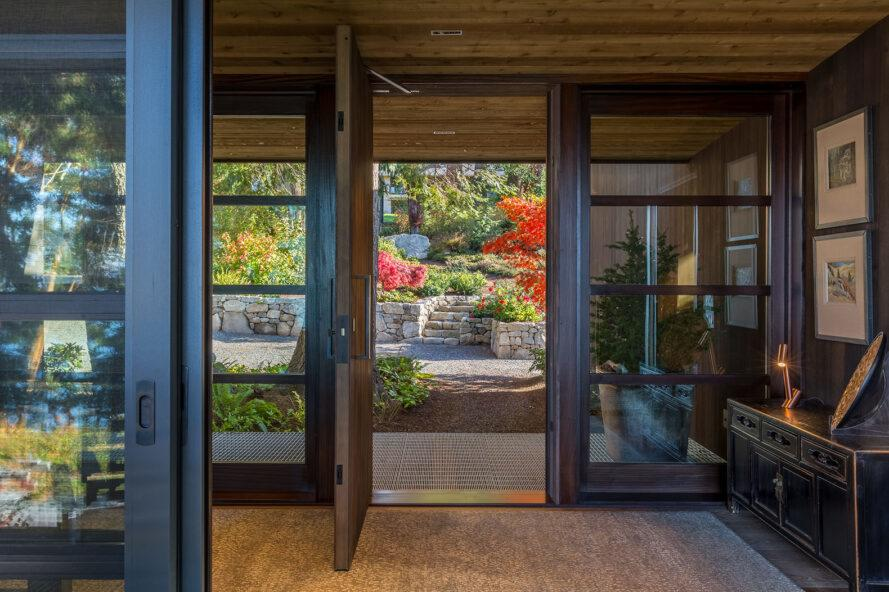 the inside of a home with open doors looking out on a garden