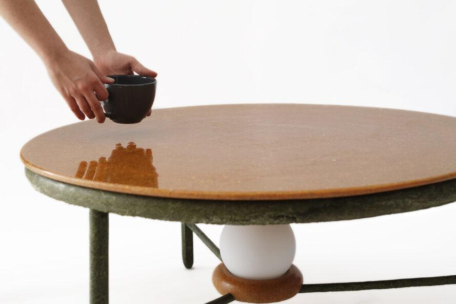 a coffee table with a brown top and dark green accents and legs. underneath the table is an attached, round lightbulb, unlit. a pair of hands are setting down a dark coffee mug on the table.