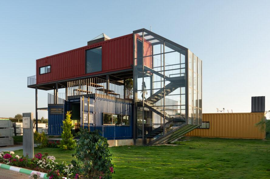 yellow, blue and red shipping containers connected by a glass-enclosed staircase