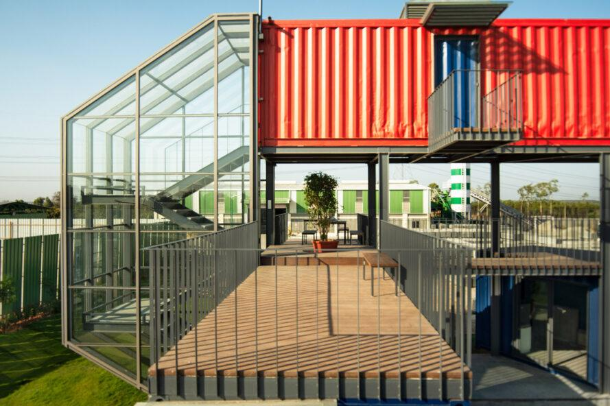 open-air walkway beneath an elevated red shipping container