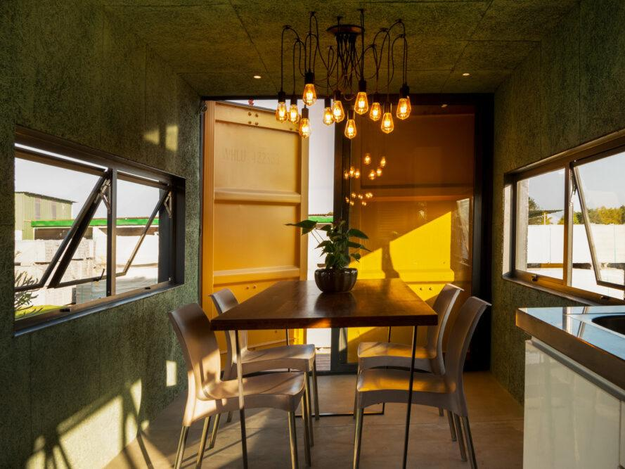 yellow room with small dining table under a modern chandelier