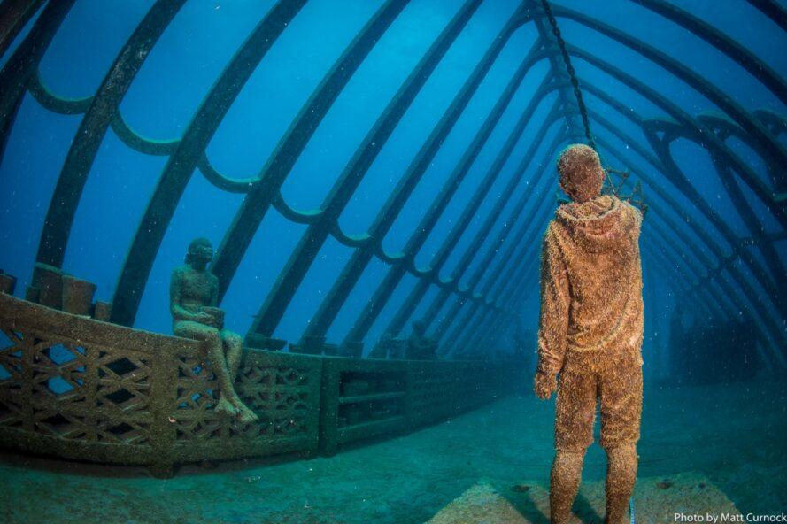 statues of people relaxing in an underwater greenhouse