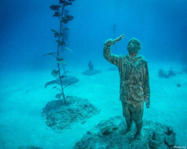 underwater statue of child holding a fish