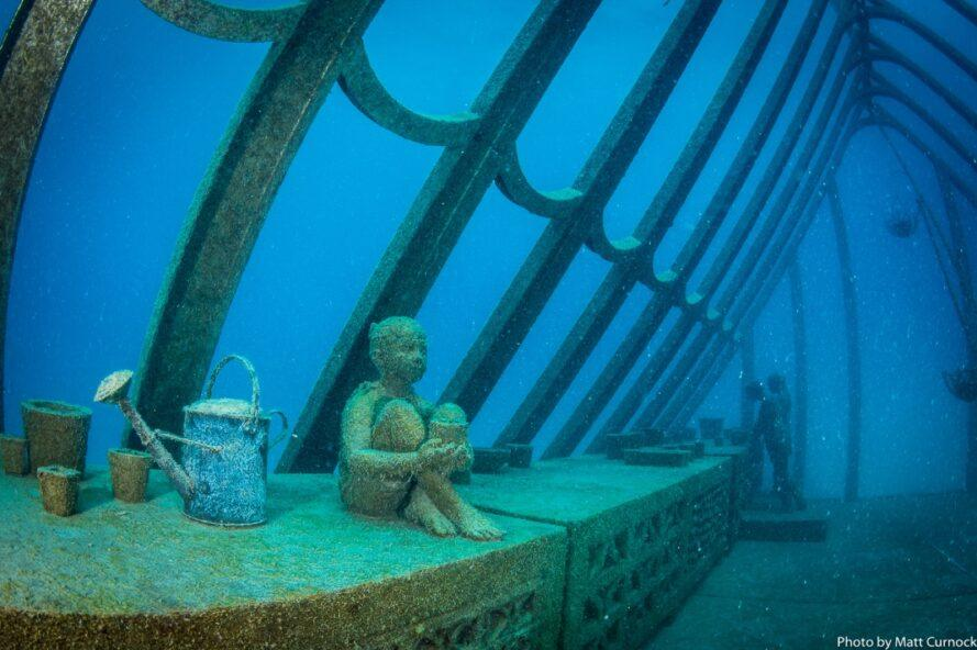 statue of child sitting near a watering can in an underwater greenhouse