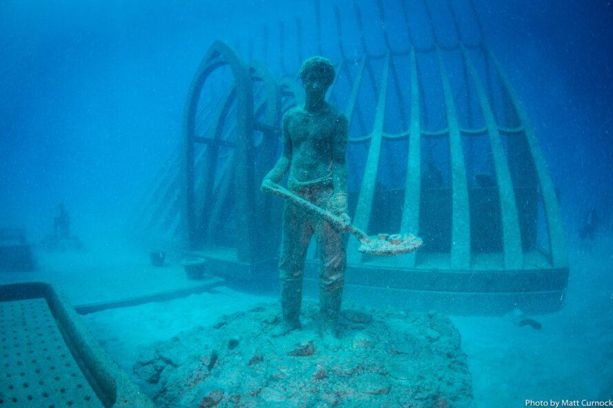 statue of person with shovel underwater
