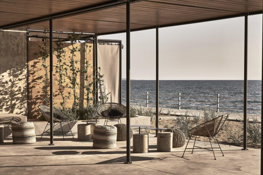 round wicker chairs on a covered patio facing the sea
