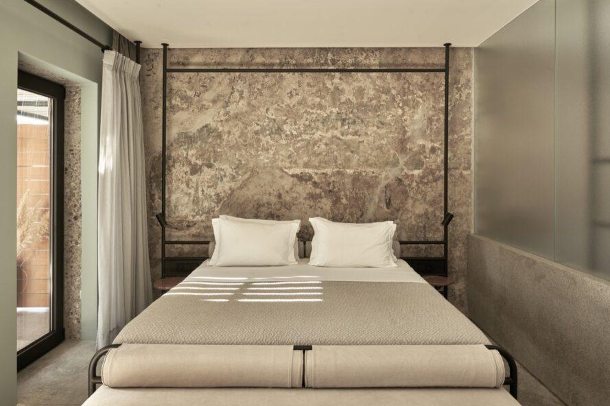 large beige bed in front of a stone wall