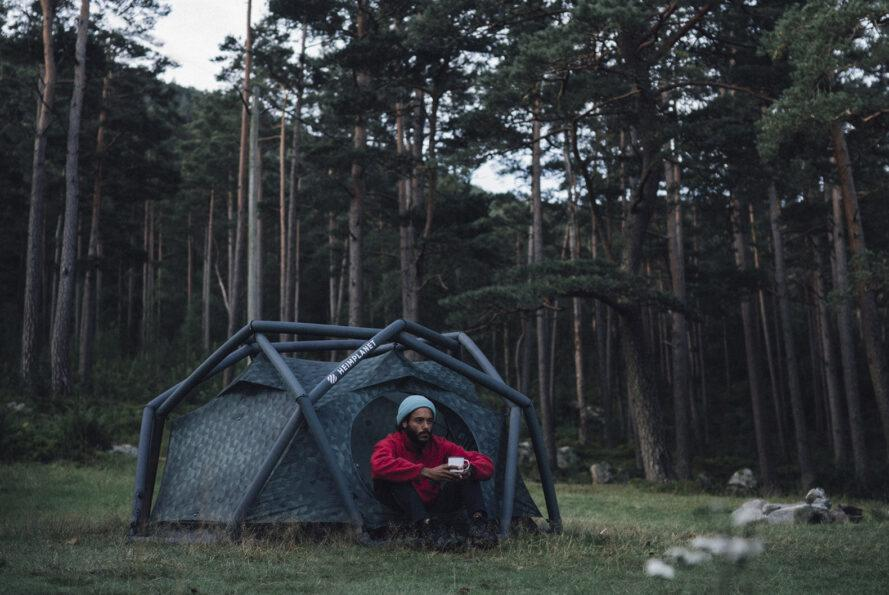 a dark colored geodesic tent set up in the middle of a forest with a person in a red shirt holding a mug sitting outside the entrance to the tent