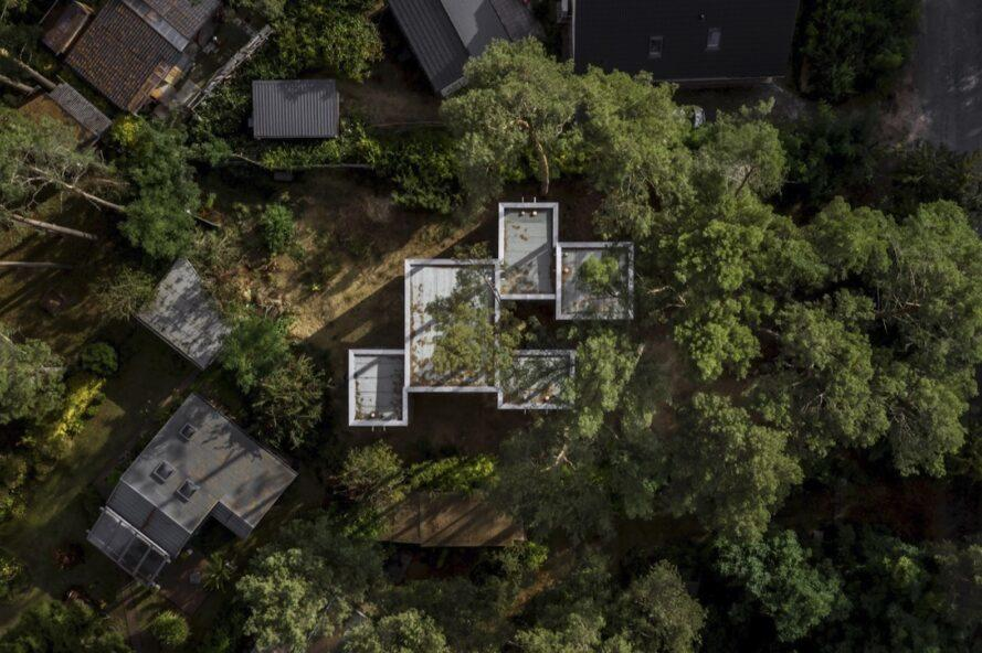 aerial view of home with multiple cube volumes in a forest