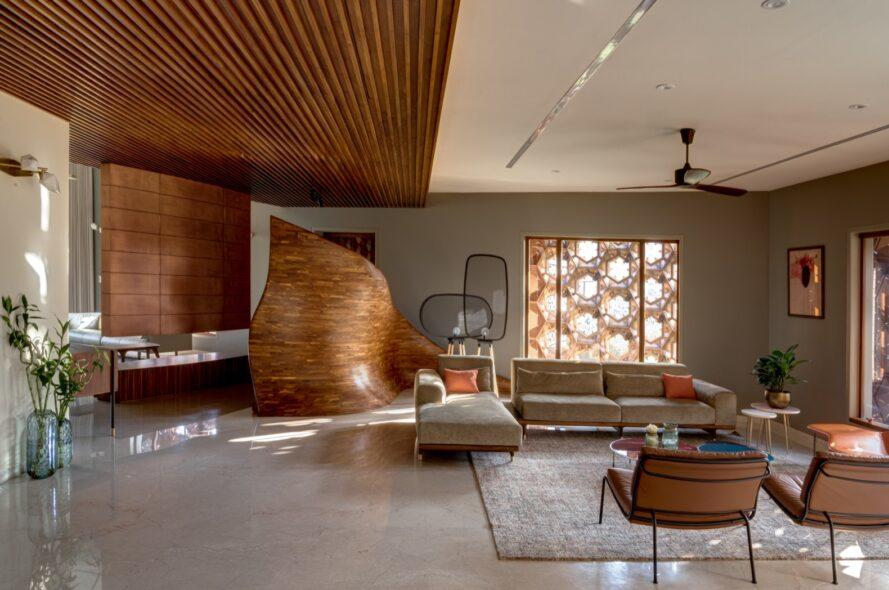 a living room with wood features, including a wave-like divider that separates the TV area and the sitting area with the L-shaped sofa.