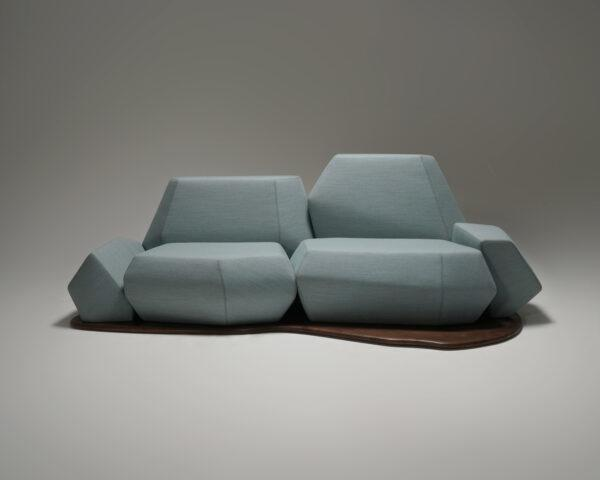 geometric light blue sofa with a curvy wooden base on a white background