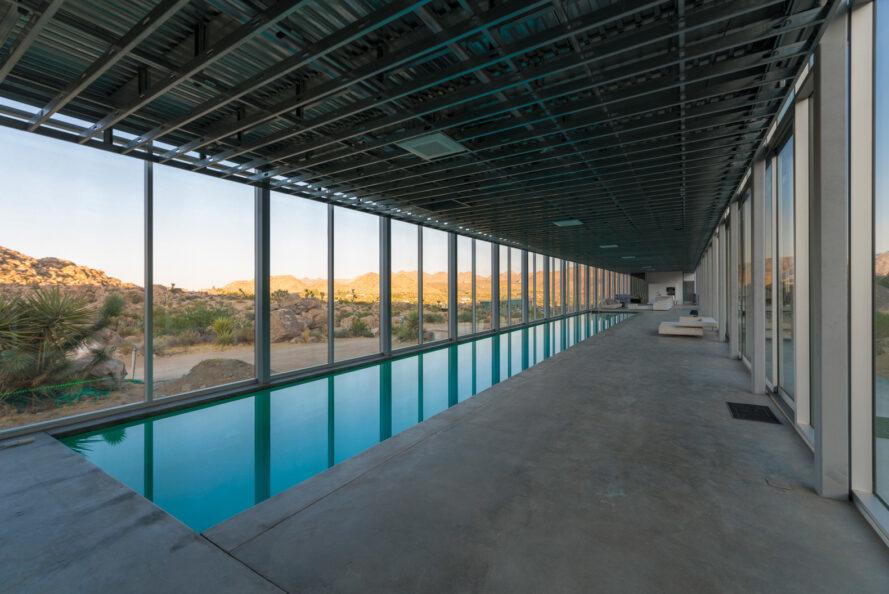 long, narrow pool in room with glass walls