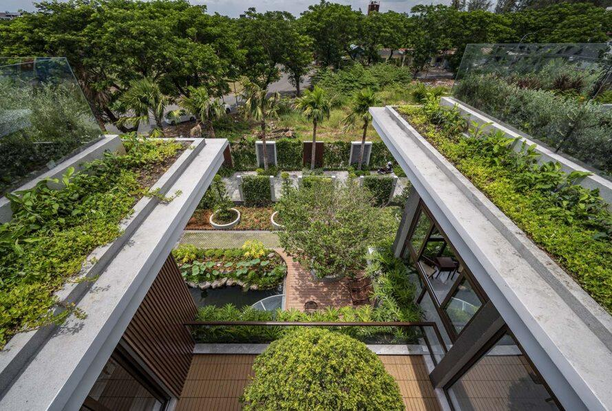 green rooftops with a courtyard between them and a garden area visible on the ground below.