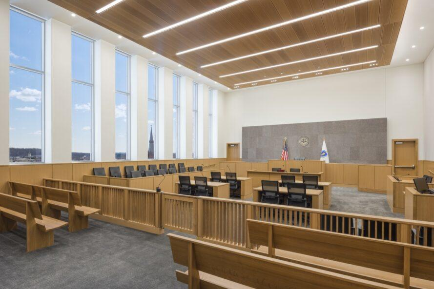 angled room of courtroom with wood benches and wood tables