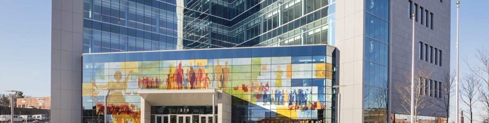 concrete and glass building with mural of people on the front
