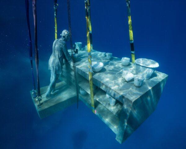 an underwater statue of a person next to a countertop covered in dishes