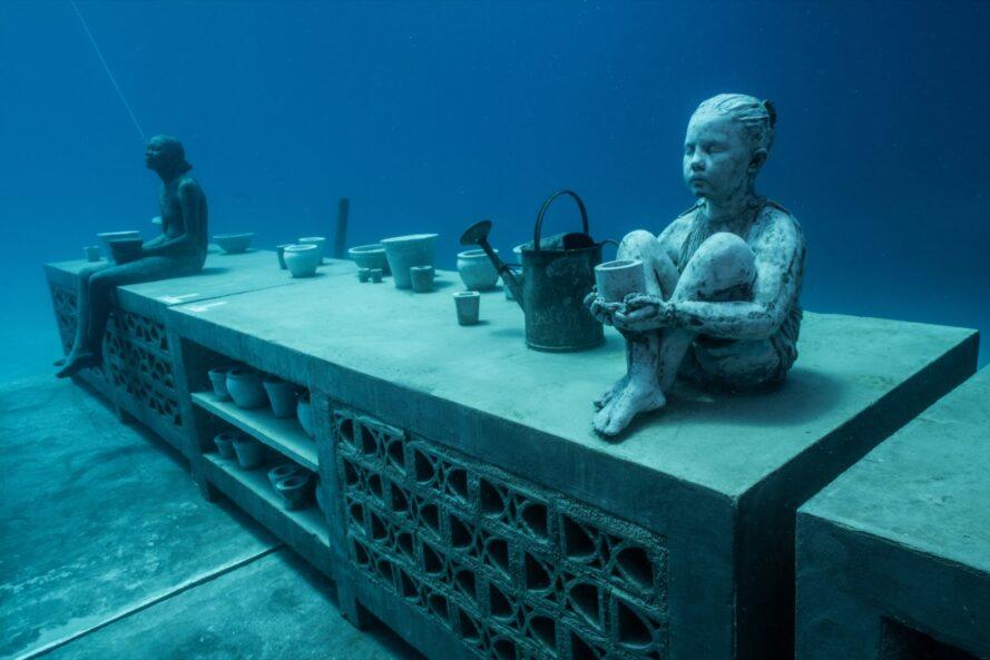 an underwater statue of a person sitting on top of a cabinet