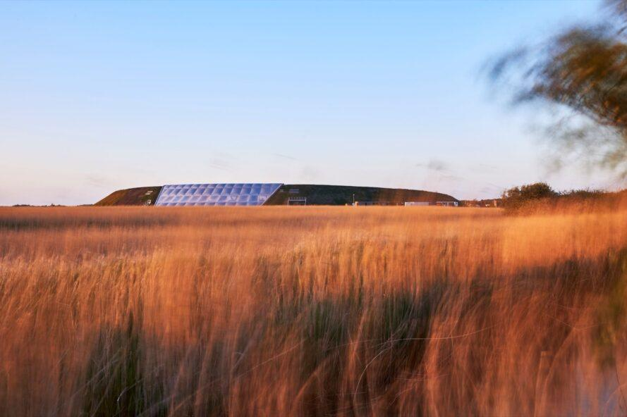 large hill with a white ETFE structure built into the center surrounded by tall grasses