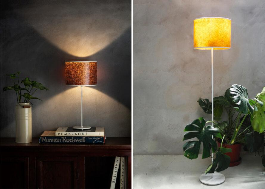 two images: to the left, a lamp with a red-brown lampshade that casts light above and below onto a table full of books. to the right, a standing lamp with an orange-yellow lampshade. a green plant sits behind the lamp.