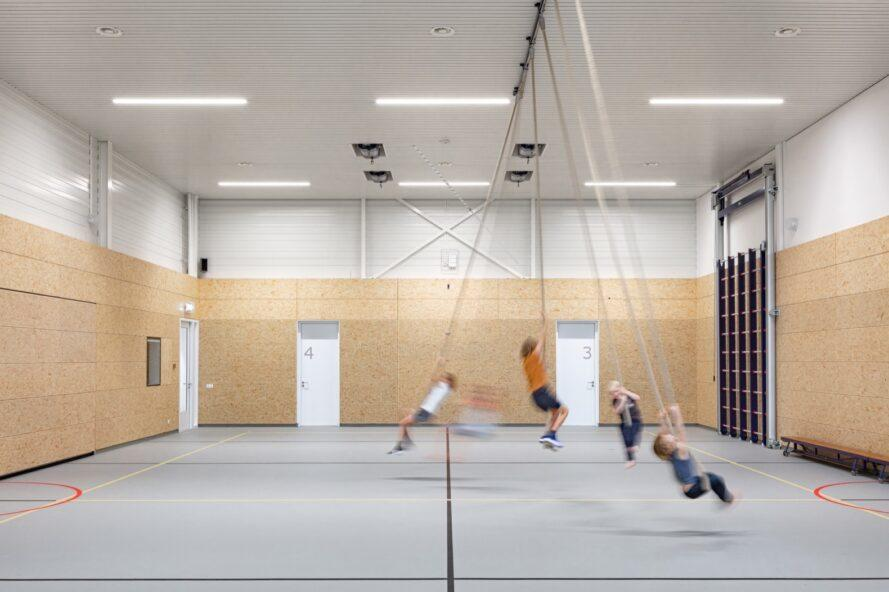 kids swinging on ropes in a gymnasium