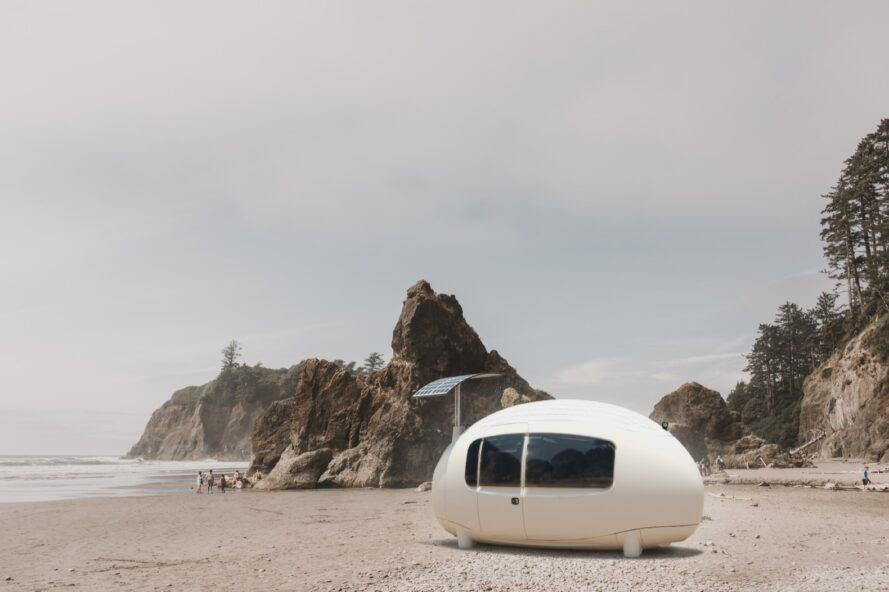 an egg-shaped white unit with windows and solar panels. in the background is a rocky beach