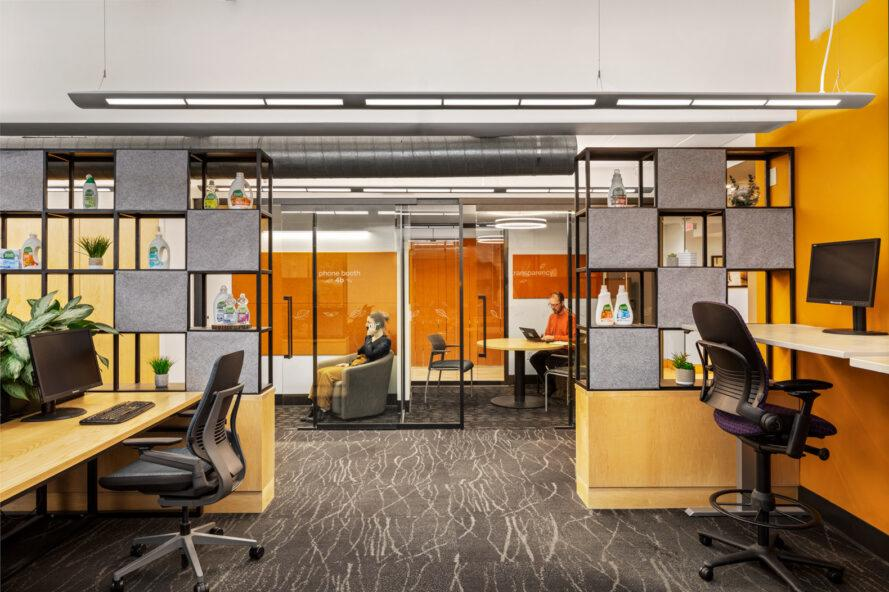 office space with wood desks and glass walls revealing orange meeting rooms