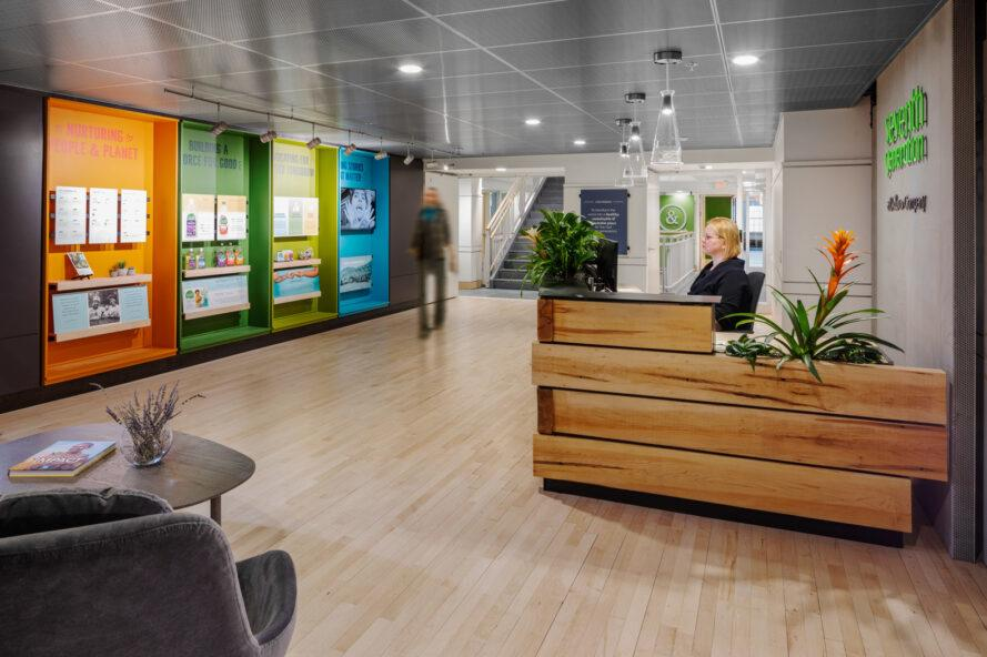 office reception area with wood desk and colorful wall display of Seventh Generation products and values