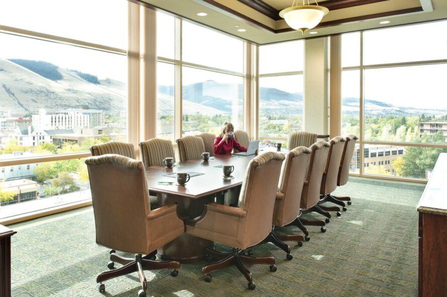 large meeting table with tan chairs in office with glass walls