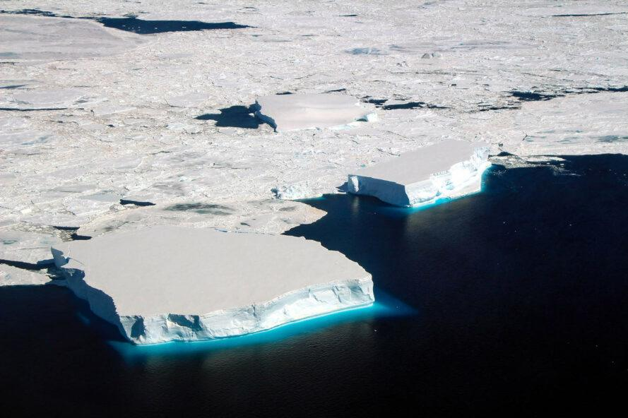 sea ice in the Antarctic, white patches of ice against deep blue water