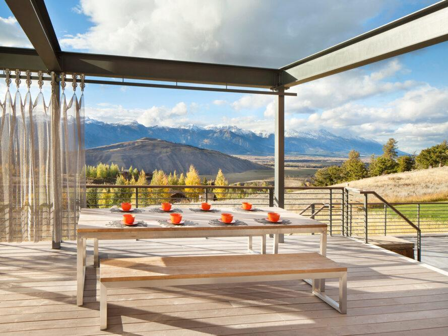 large wood table and benches on an open-air deck