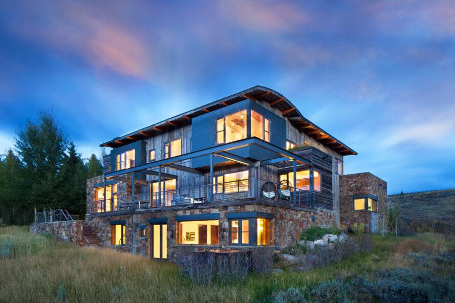 three-story home with wood and stone exterior at dusk