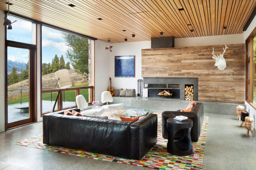 living room with wood ceilings and walls and two black leather sofas facing a fireplace