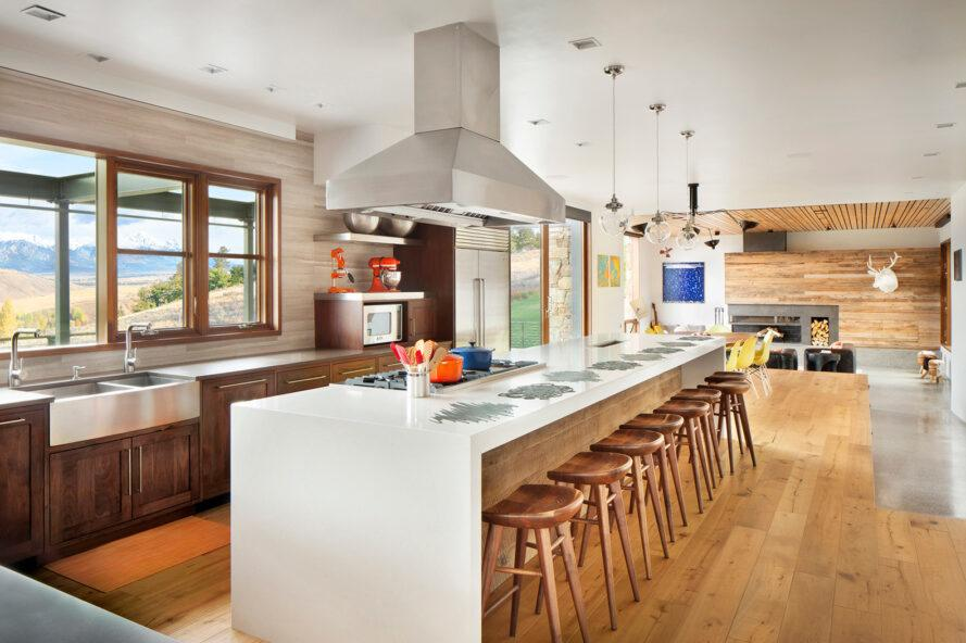 long white island with several wood bar stools